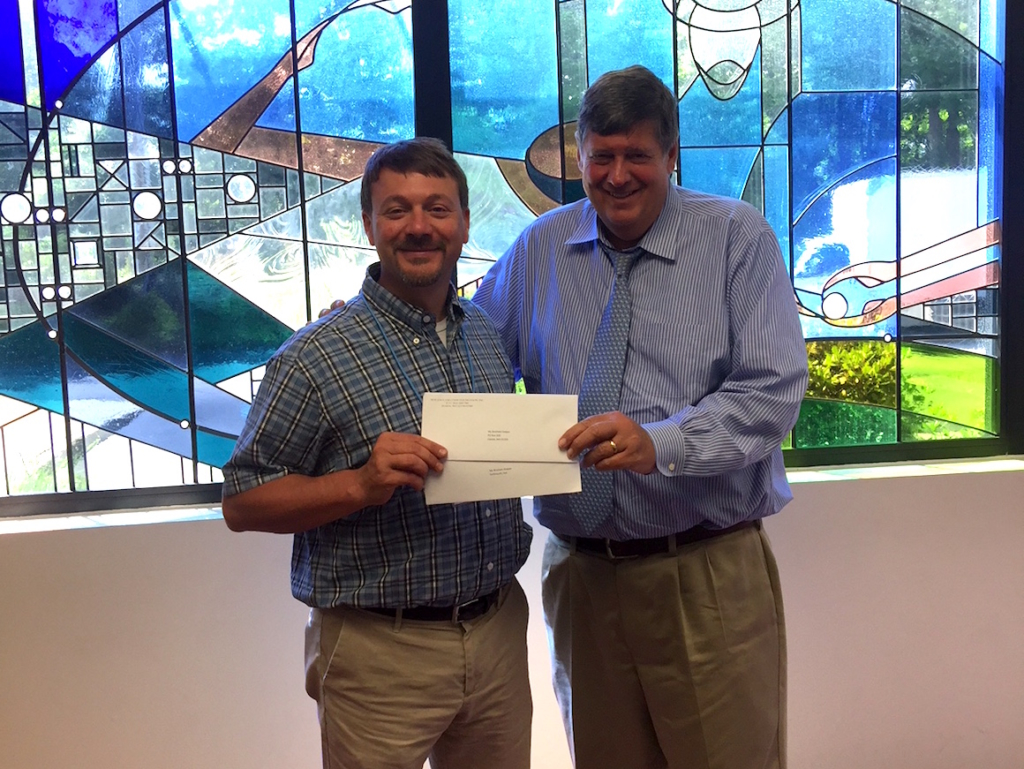 President of My Brother's Keeper, holding check alongside president of New England Food Foundation
