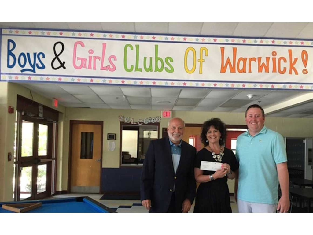 Representative of Boys and Girls Club of Warwick, holding check alongside executives from New England Food Foundation
